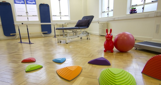 Interior shot of Manchester OT clinic with stepping blocks on the ground for therapy.