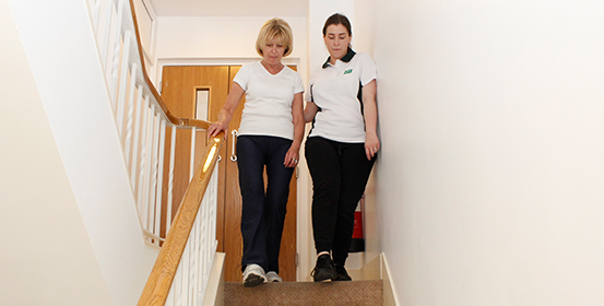 Therapist helps ManchesterOT patient down stairs.