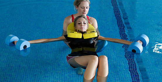 ManchesterOT therapist aids a patient during a hydrotherapy session with floats.