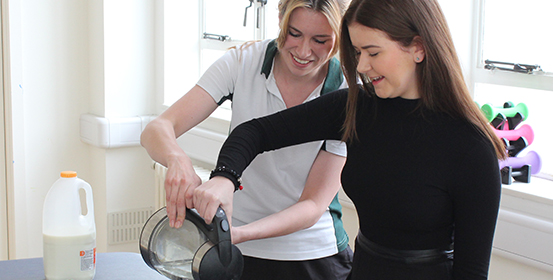 ManchesterOT therapist helps patient complete everyday task as part of her therapy.