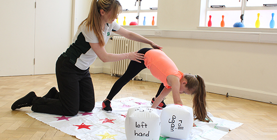 Young child using twister style game to stretch with therapist.