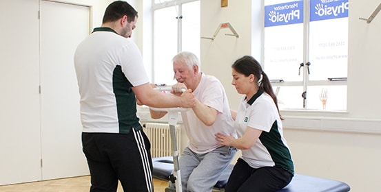 Elderly patient gets help standing; by two trained ManchesterOT therapists.