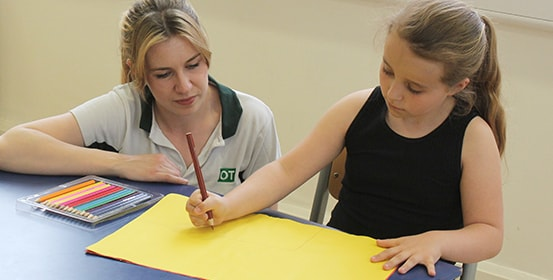 Young child gets help with improving her handwriting during a ManchesterOT therapy session.